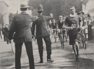 Photograph of the marathon race showing two London policemen cautioning cyclists