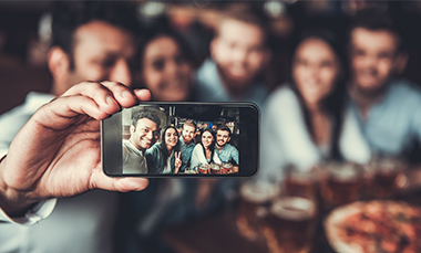 A stock image of a group of people taking a selfie