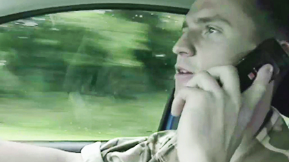 Still from the Grim Reaper video showing an army officer driving while talking on a mobile phone