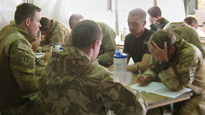 Members of the UK armed services attending a meeting in a tent