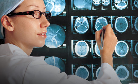 Female researcher pointing at backlit brain scans