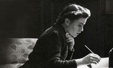 photograph of woman at a desk in profile with a pen in hand reading or writing probably from 1930s