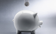 White piggy bank with money dropping into it