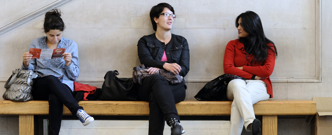 three students on bench in foyer