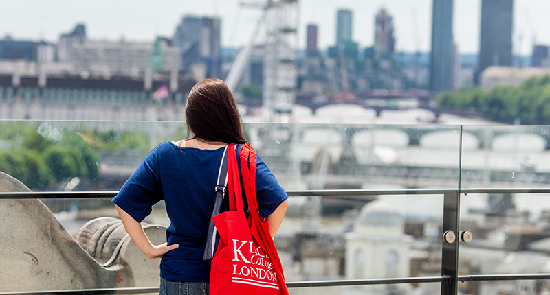 A student standing on the roof deck of Bush House looking out over London.