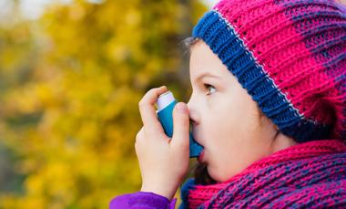 A young girl using an asthma inhaler.