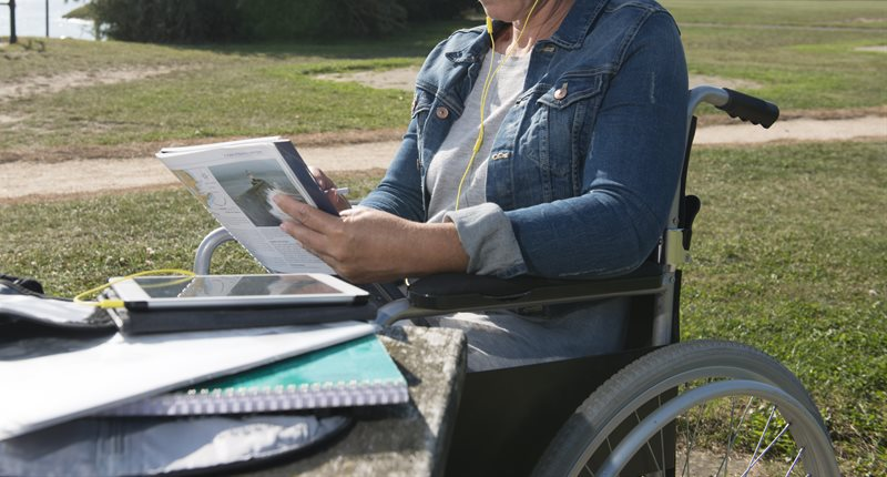Woman in a wheelchair reading in a park.