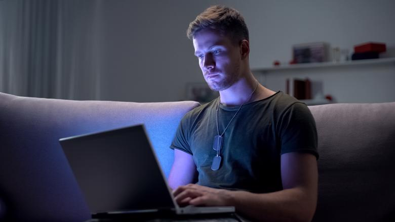 Young military man sat on a sofa looking at a laptop