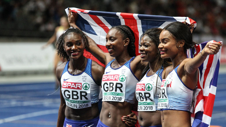The Team GB women's relay team celebrate victory, four women hold up a flag behind them