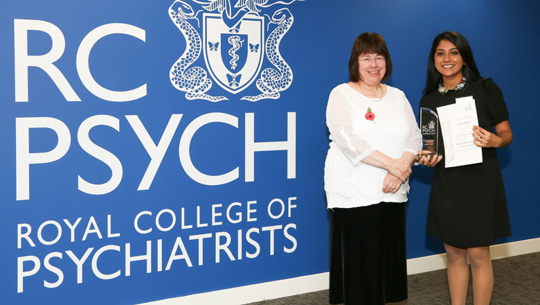 Two people pose in front of the Royal College of Psychiatry logo