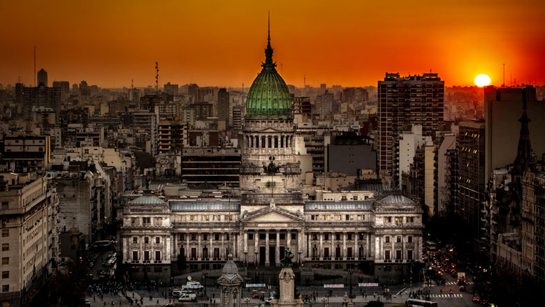 An edited image shows a deep orange sunset over an aerial view of the palatial Argentine National Congress