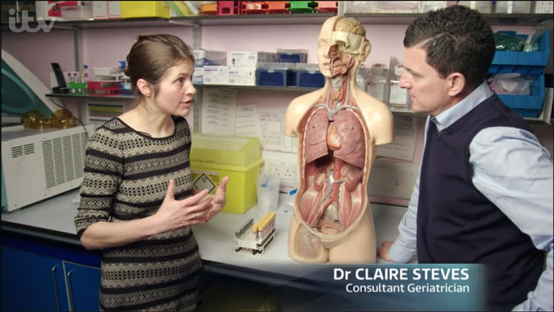 Dr Claire Steves interviewed for ITV with a model of human lungs in background