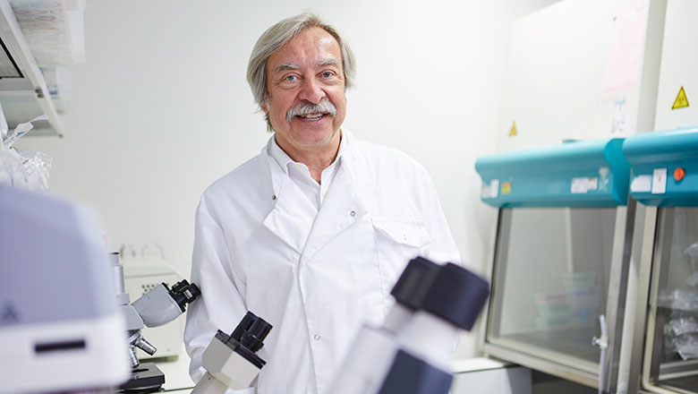 An older man in a white lab coat