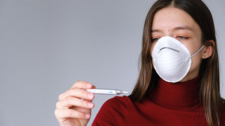 A woman in a face mask reads a thermometer