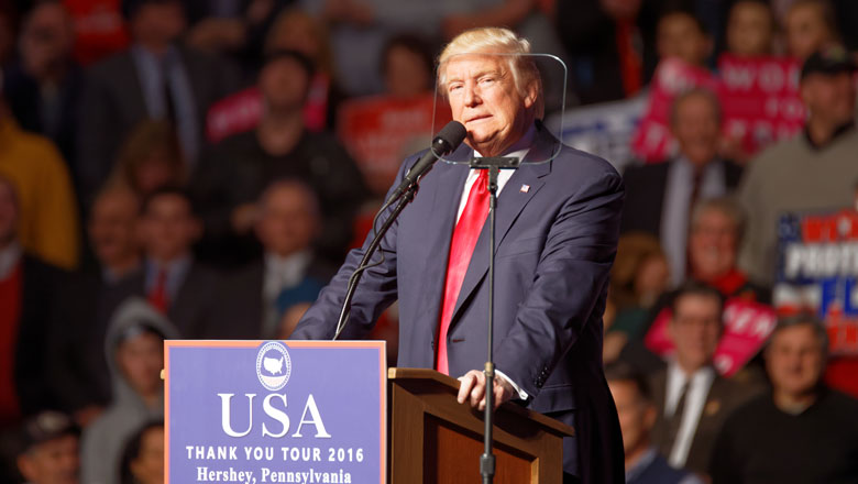 Donald Trump stands at a podium in 2016 on his post-election victory tour