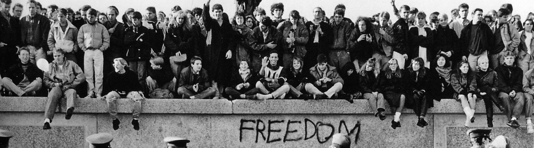 East German students sit atop the Berlin Wall at the Brandenburg Gate in front of border guards