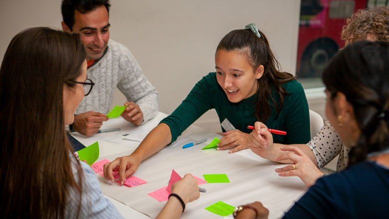 A group chats and arranges brightly coloured post-it notes