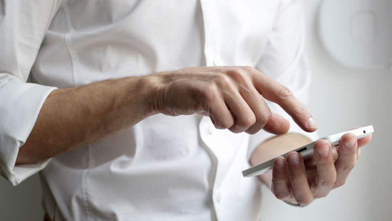 man wearing a white shirt holding a white Android smartphone