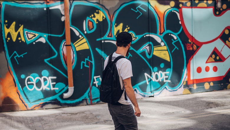 Man with backpack standing in front of graffiti wall