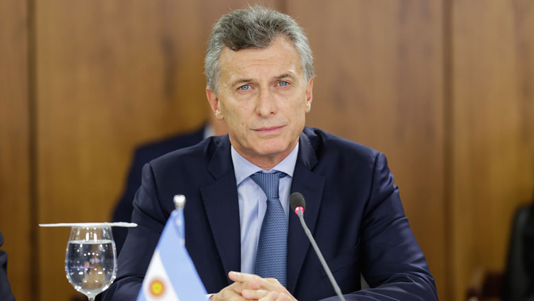 The former president of Argentina Mauricio Macri sits at a conference table behind a small flag and a microphone
