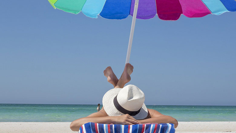 Person sunbathing under an umbrella on a beach