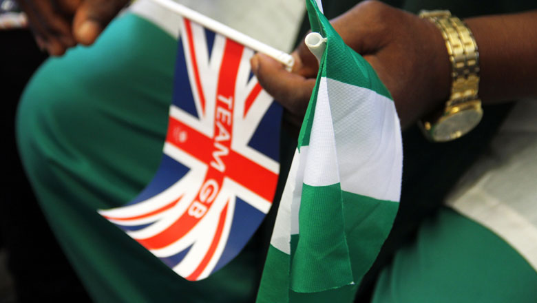 man holding the Union Jack and Nigerian flag in his hands