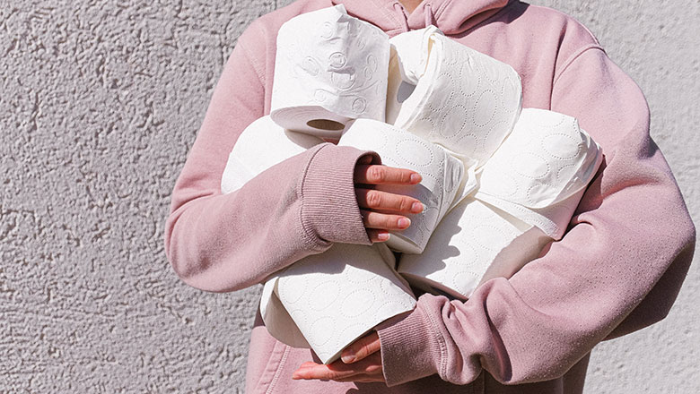 A woman in a pink hoody grasps several loo rolls in her folded arms