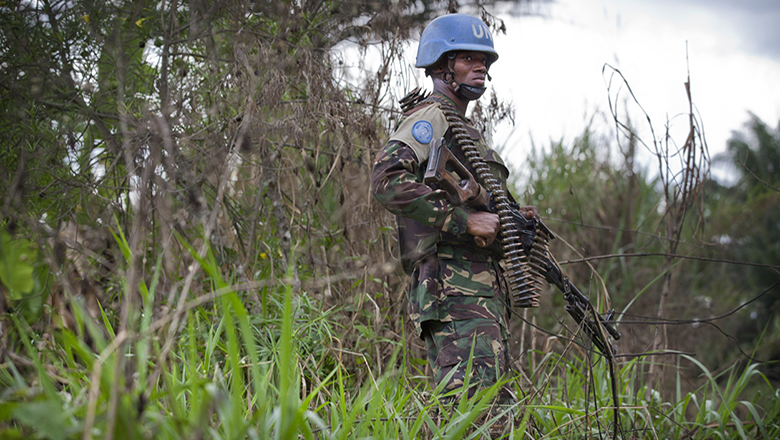 A UN peacekeeper stands in a grassy wooded area in DRC
