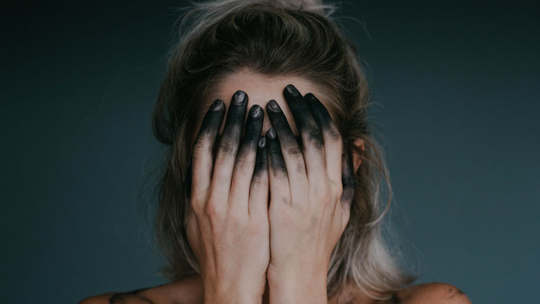 Woman covering face with ink stained hands