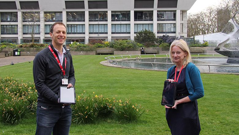 Joel Meyer and Louise Rose holding tablet devices outside St Thomas' Hospital in London.