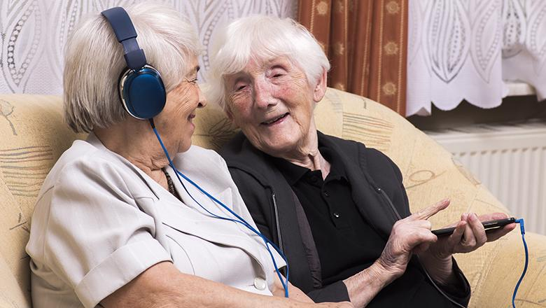 Older people with device and headphones