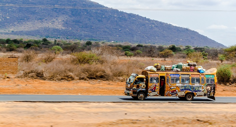 Brightly coloured bus in an African landscape