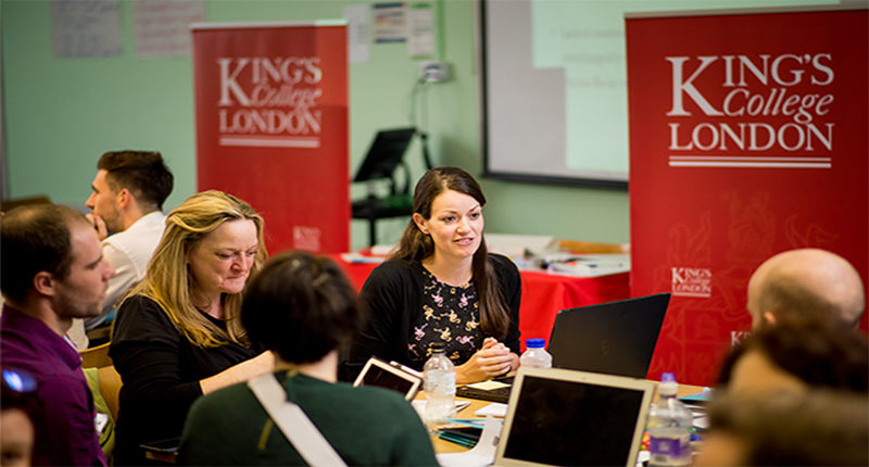 Students around a table with two red King's banners in the background