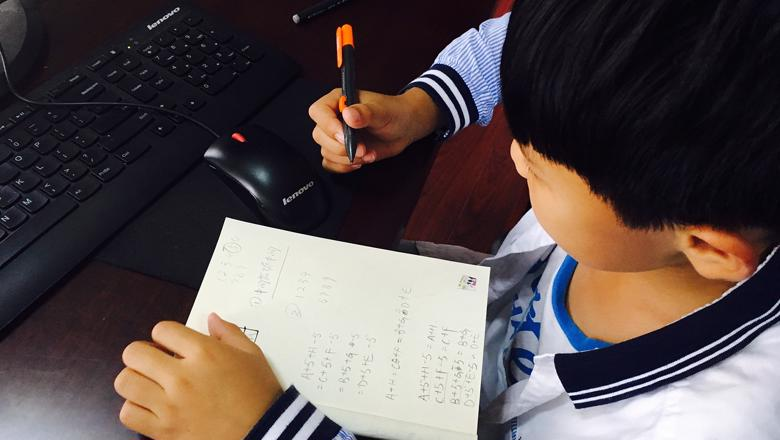 Child working at a computer with a pen and notepad