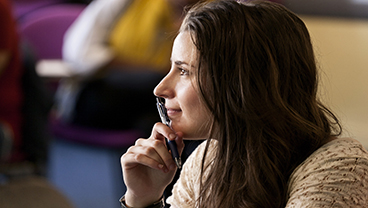 Student listening with a pen to her mouth