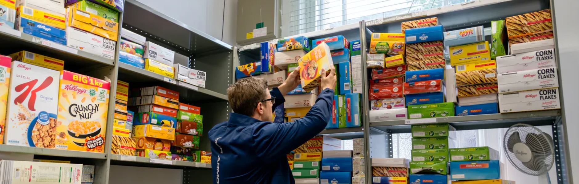 Man reaches for groceries off a shelf in a food bank