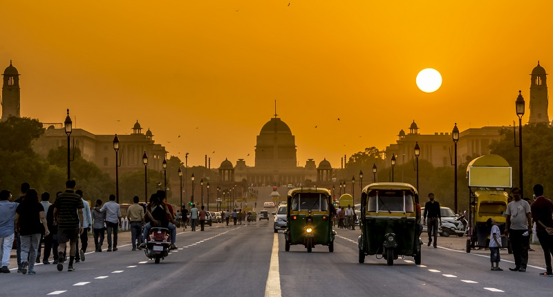 Vehicles in India against an orange sky