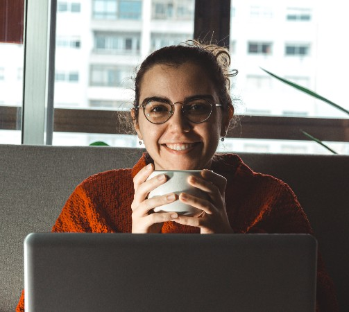 MINI PROMO Student smiling on laptop with cup